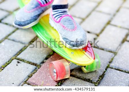 Legs of skateboarder kid girl on colorful skateboard in the park - stock photo