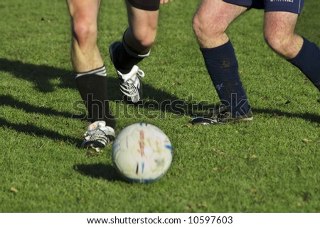 legs of soccer players in action on grass - stock photo