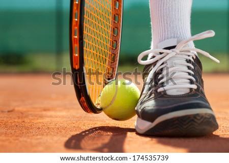 Legs of sportive man  near the tennis racquet and balls - stock photo