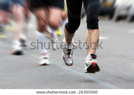 Legs of sportsmen running marathon in action, motion blur - stock photo