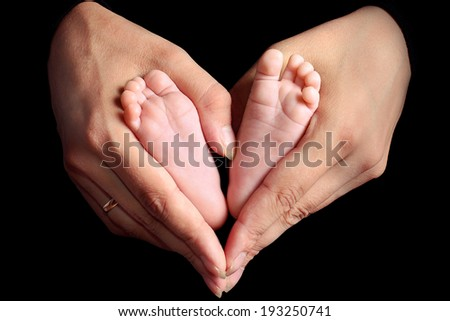 legs of the newborn child in hands of careful mother,  black background