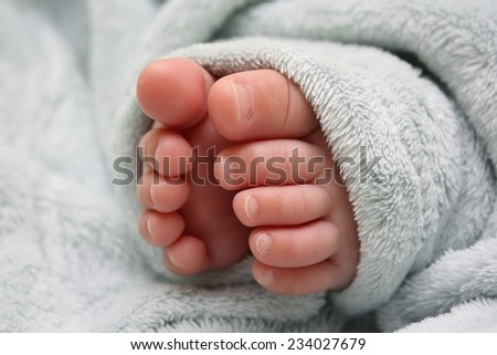 Legs of the sleeping baby in blue fluffy blanket - stock photo