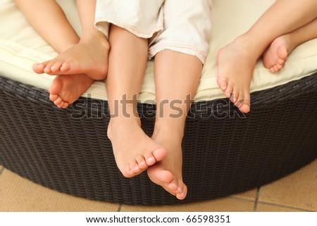 legs of three barefooted children lying on circle sofa - stock photo