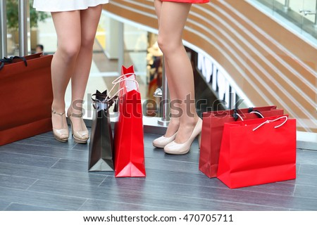 Legs of two beautiful girls standing with bags in shopping center
