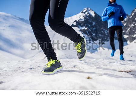 Legs of two runners outside in winter nature - stock photo