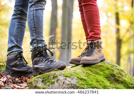 Legs of unrecognizable man and woman in autumn nature