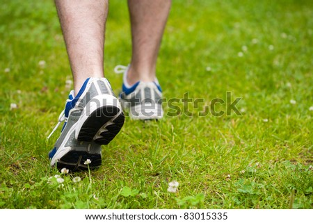 legs of walking man on grass - stock photo
