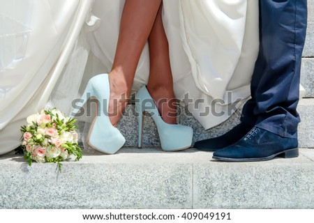 Legs of wedding couple on stone stairs and bouquet - stock photo