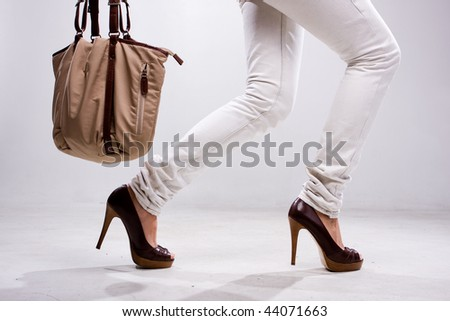 Legs of woman and bag at white background - stock photo
