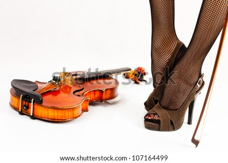 Legs of woman and her violin - stock photo