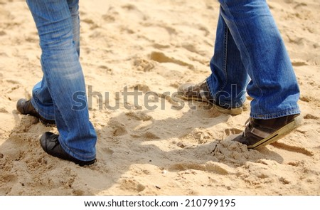Legs of woman and man on the beach, couple walking in comfortable shoes outdoor on the beach in summer, summer time - stock photo
