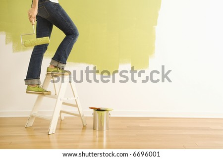 Legs of woman climbing stepladder holding paint roller.