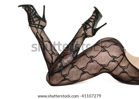 Legs of woman in sexy body stockings and stilettos lying on white background - stock photo