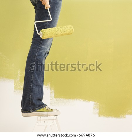 Legs of woman standing on stepladder holding paint roller with painted wall.