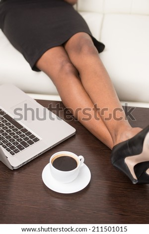 legs of young black girl with laptop computer. Woman sitting in bright living room on sofa with feet on table - stock photo