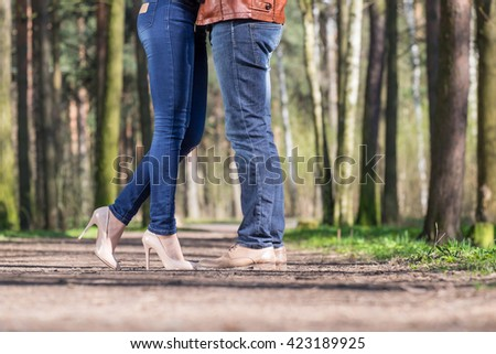 Legs of young couple in spring park - stock photo