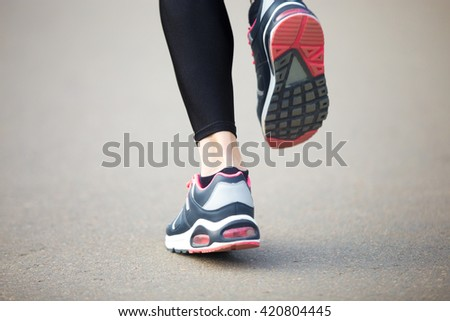 Legs of young female model running in park during everyday practice. Fitness woman in training shoes jogging outdoors in park. Sport active lifestyle concept. Back view. Close-up - stock photo