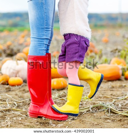 Legs of young woman and her little kid girl daugher in rainboots. Woman in red gum boots, child in yellow shoes. On pumpkin field, outdoors. - stock photo