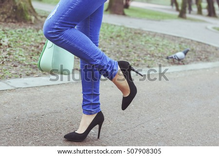Legs of young woman in blue ragged jeans and black suede high-heeled shoes. Girl with green bag in hand for a walk in the park. Spring trendy fashion look