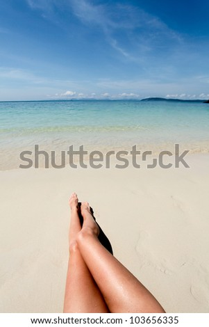 Legs of young woman lying in the sand on the beach against of ocean and sky - stock photo