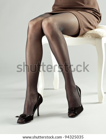 Legs of young woman wearing mini dress and high-heeled black shoes - stock photo