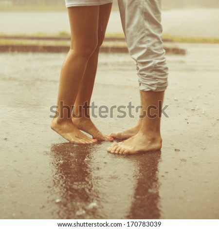 Legs on beach. Foot spa. A loving young couple hugging and kissing under a rain. Two lovers, man and woman barefoot in the shower. Summer in love - stock photo