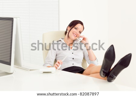 Legs on table relax pose smiling professional businesswoman calling phone