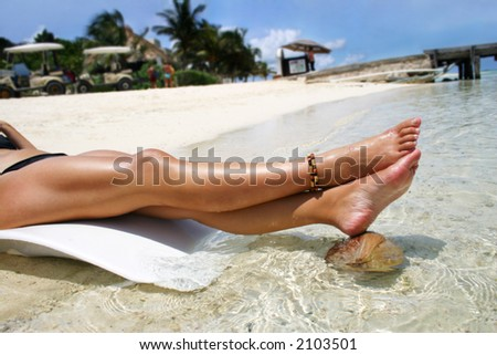 Legs on tropical beach - stock photo