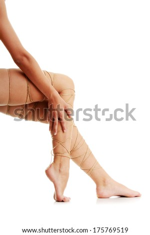 Legs pain concept - legs tied with rope isolated on white - stock photo