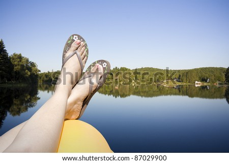 Legs resting on a paddle boat in calm lake water shot in muskoka cottage country ontario