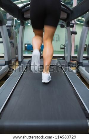 Legs running on a treadmill - stock photo