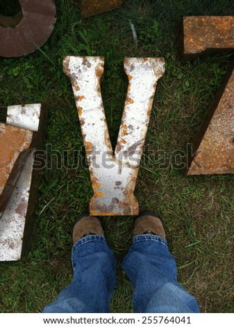 "Legs standing over a rusty metal letter ""V"" - stock photo"