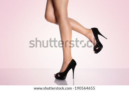 legs with black high-heeled shoes on a pink background - stock photo