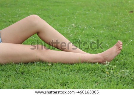 Legs woman relaxing on grass.