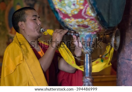 Leh, India â?? AUGUST 23, 2007: Buddhist monk playing traditional instrument during buddhist ceremony at Thiksay monastery. - stock photo