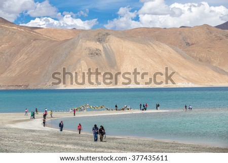 LEH, INDIA - AUGUST 6,2015 : Tourists walking at Pangong Lake, Leh India. Pangong Lake is an endorheic lake in the Himalayas situated at a height of about 4,350 m.