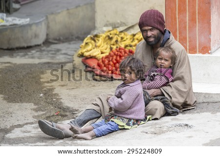 LEH, INDIA - JUNE 29, 2015: Unidentified poor Indian beggar family on street in Ladakh. Children of the early ages are often brought to the begging profession. - stock photo