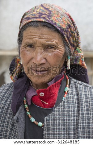 LEH, INDIA - JUNE 24, 2015: Unknown beggar woman begging on the street in Leh, Ladakh. Poverty is a major issue in India - stock photo