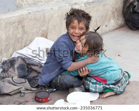 LEH, INDIA - SEPTEMBER 08 2014: An unidentified beggar girl and boy begs for money from a passerby in Leh. Poverty is a major issue in India  - stock photo