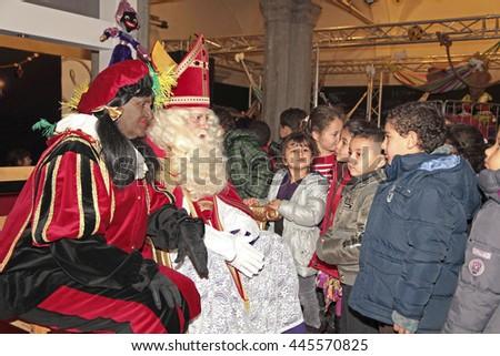 Leiden, The Netherlands - November 2011: Dutch children visite Black Pete and Sinterklaas  , dutch characters, in the house of Sinterklaas - stock photo