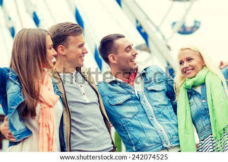 leisure, amusement park and friendship concept - group of smiling friends ferris wheel on the back - stock photo