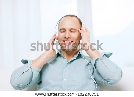 leisure and lifestyle concept - happy man with headphones listening to music at home - stock photo