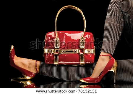 Leisure bag. A close-up of a chic red handbag along with sexy female legs wearing elegant red shoes. - stock photo