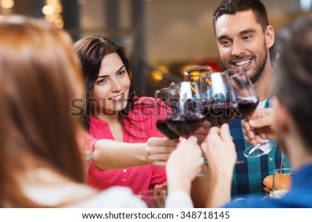 leisure, celebration, drinks, people and holidays concept - happy couple and friends clinking glasses of wine at restaurant - stock photo
