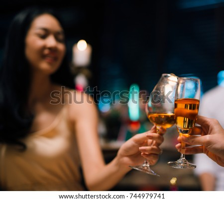 leisure, celebration, drinks, people and holidays concept - happy couple and friends clinking glasses of wine at restaurant bar