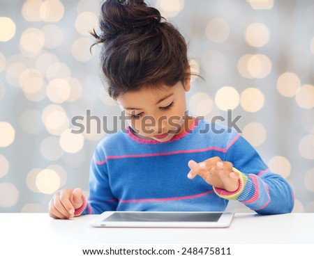 leisure, childhood, technology and people concept - little girl with tablet pc over holidays lights background