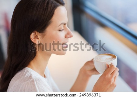 leisure, drinks, people and lifestyle concept - close up of smiling young woman drinking coffee at cafe - stock photo