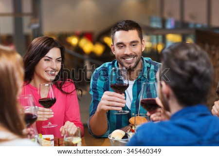 leisure, eating, food and drinks, people and holidays concept - smiling friends having dinner and drinking red wine at restaurant - stock photo
