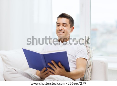 leisure, education, literature and people concept - happy man reading book at home - stock photo
