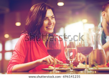leisure, food and drinks, people and holidays concept - happy woman with friends having dinner at restaurant